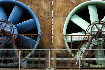 Stock photo of two big fans, from https://www.pexels.com/photo/blue-plastic-bucket-on-brown-wooden-wall-5502720/